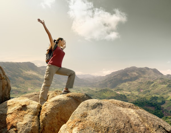 Hiker with backpack standing on top of a mountain with raised hands and enjoying landscape.